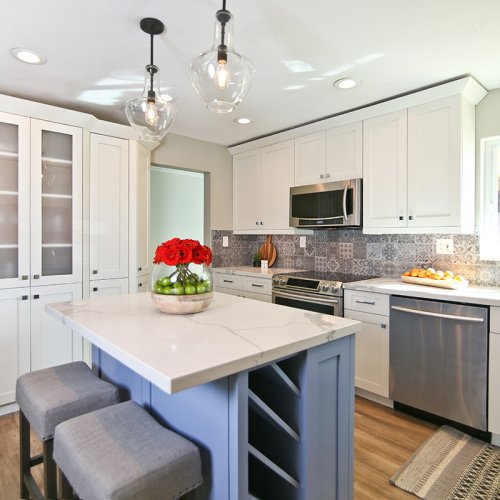 Contemporary kitchen with white cabinets and blue island
