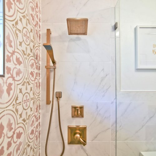 Pink and white cement tiles with gold fixtures